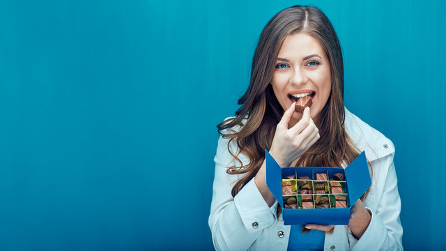 Happy young woman eating chocolate candies.