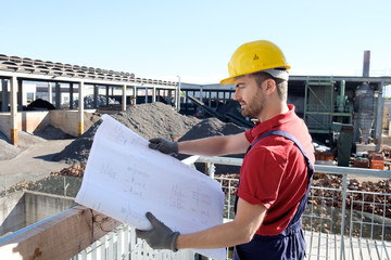Portrait of factory worker on building site background