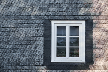 White casement window with mullions, fastened in a black building facade made of slate shingles