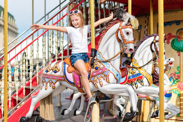 Girl riding on a merry go round. Little girl playing on carousel, summer fun, happy childhood and vacation concept