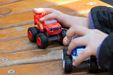 Happy child holding in hands two car toys wooden road at the playground outdoors.
