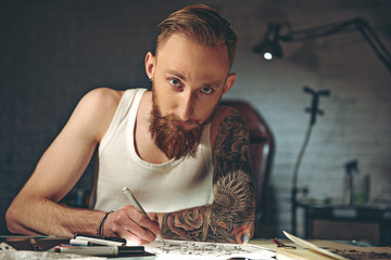 Calm bearded man drawing picture