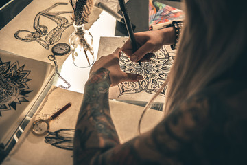 Female drawing unusual images at desk