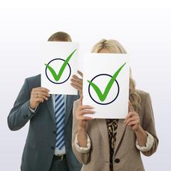 Ein Paar,  das sich ein Blatt Papier mit grünen Häkchen vor das Gesicht hält