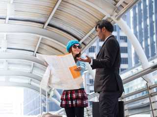 Asian businessman helping  woman traveler carefully reading the map of the city. Travel and tourism concept.