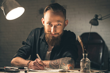 Outgoing young man drawing pictures at desk
