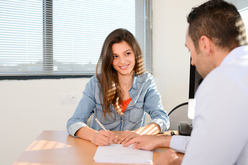 beautiful young woman in office with professional finance businessman buying contract signature