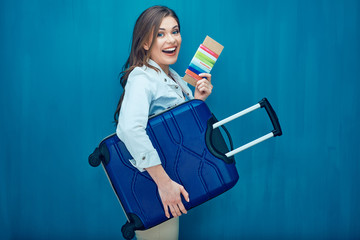 Smiling young woman holding suitcase, passport, ticket
