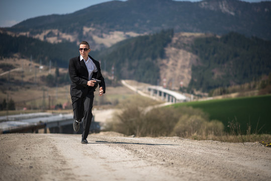 Agent in a suit holding a gun and running at a highway construction site in James Bond movie style.