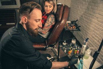 Calm male master putting color in tattoo machine