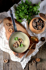 Healthy Mushroom cream soup with celery and parsley on an old wooden background. Rustic style.