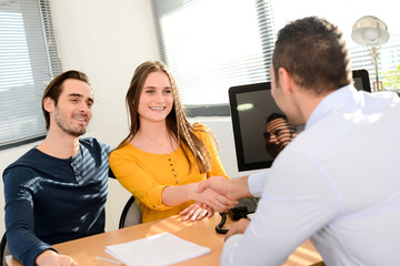 hand shaking and buying agreement contract signature between a young couple and a professional finance business man in office