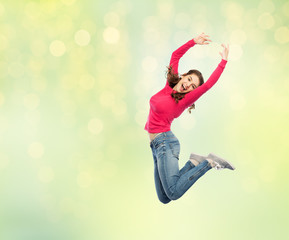happy young woman jumping in air or dancing