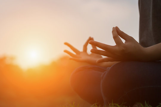 Close up of young woman doing yoga in the park with sunset