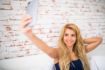 Beautiful girl making selfie on the bed at home against brick wall