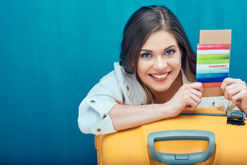 Close up smiling face portrait of young woman holding passport with ticket