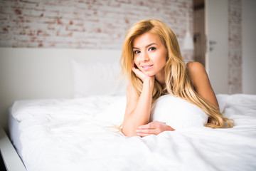 Beautiful young girl posing on the bed at home