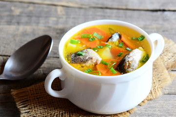 Healthy and nutritious fish soup. Slow cooked hearty fish soup with vegetables in a bowl. Vintage wooden background. Closeup