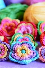 Crochet multi-colored flowers set. Crochet flower motifs and patterns. Interesting hobby for women and children. Closeup. Vertical photo