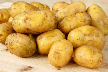 Raw new potatoes with peeling on a wooden background