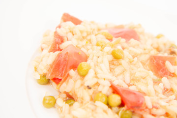 Risotto with tomato and pea on a white background