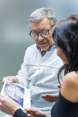 Patient and dentist holding xray. Dental doctor consulting a woman. Things you need to know.
