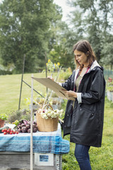 Mid adult woman writing on cardboard while standing by freshly harvested vegetables in urban garden