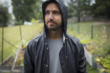 Thoughtful mid adult man wearing raincoat in vegetable garden