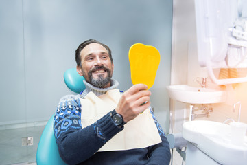 Man in dental chair. Person holding mirror and smiling. Fix your smile.