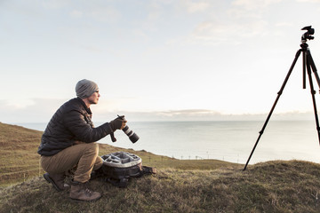 Side view of hiker looking away while holding SLR camera on hill by sea against sky