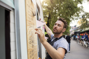 Side view of owner hanging bunting on food truck