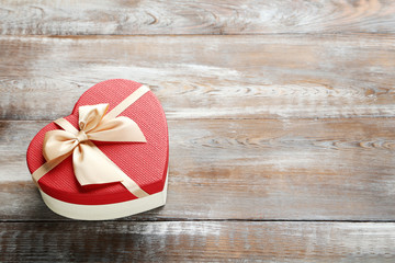 Beautiful heart gift box on a brown wooden table
