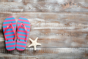 Flip flops with starfish on a brown wooden table