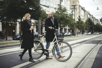 Full length of business people with bicycle crossing city street