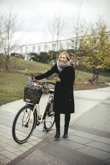 Full length of cheerful mid adult woman with bicycle on footpath