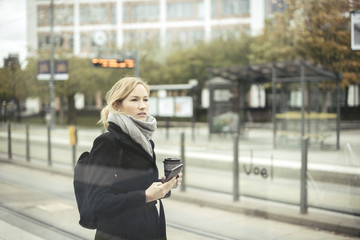 Mid adult businesswoman holding mobile phone and disposable coffee cup at tram station