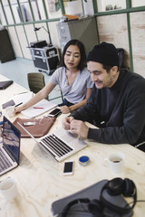 Young woman and man using laptop at desk in office