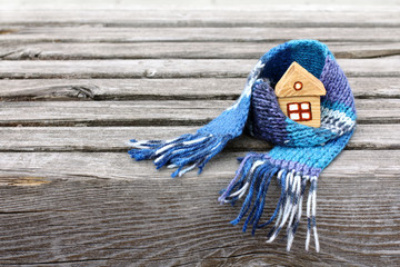 warming atmosphere for living/ Small house in a warm scarf on a very old wooden surface