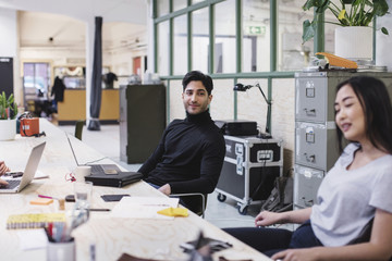 Smiling young man looking at female colleague in creative office