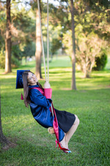 Young beautiful graduate girl with swing in the field