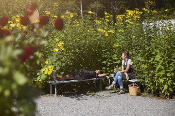 Florists resting on benches by plants