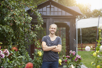 Portrait of male gardener with arms crossed smiling in yard
