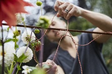 Male gardener tying string to support flowers in yard