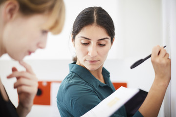 Mid adult businesswoman writing on whiteboard while colleague reading document in office