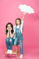 Beautiful happy mother and daughter with blank speech bubble posing on stool