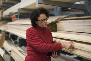 Female customer selecting wooden plank at hardware store