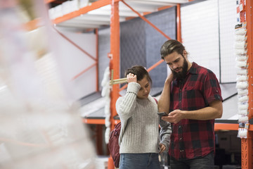 Couple using smart phone while standing in hardware store
