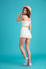 Back view of a smiling pretty girl wearing summer clothes
