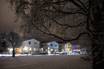 Illuminated houses by snow covered road at night