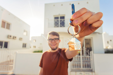 Concept of housewarming, real estate, new home - Young man holding key of new house.
